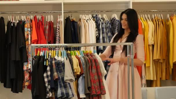 Žena je výběr že oblečení odebere Trempels nabídky Shop klienta bruneta žena je nákup oblečení v Boutique oděvy jsou zavěšené na Trempels