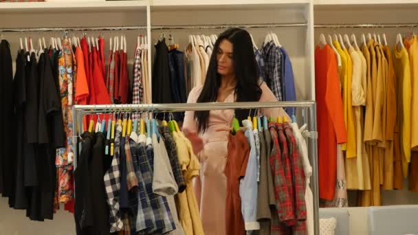Žena, výběrem oblečení dětské šaty nabídky Shop klienta bruneta žena je nákup oblečení v Boutique oděvy jsou zavěšené na Trempels