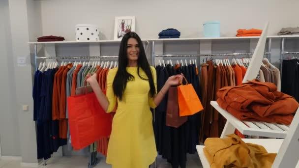 87389ef70f Nő jelentő gazdaság táskák vásárolt ruhákat sétál el női ruházat bolt  boldog ügyfél barna nő vásárol egy ruhát Boutique ruházat Trempels– stock  felvétel