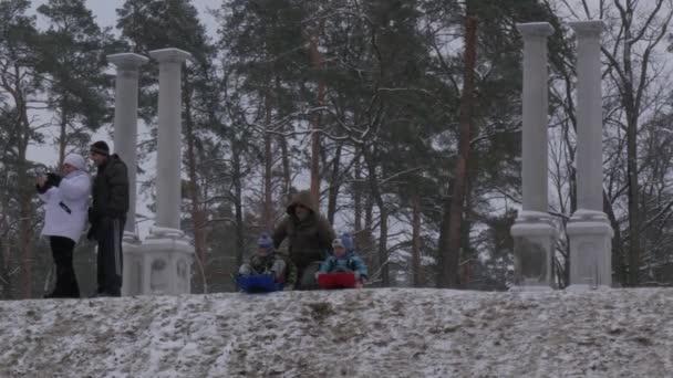 Vater-Sohn-Rides Sleigh Bucha Ukraine Weihnachtsvati seinen Sohn Fahrt Schlitten Downhill Kinder Stops revolutioniert die Sleigh Winter-Kinder und Eltern gemeinsam Lets