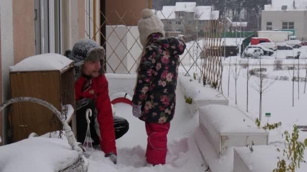 Ten kluk s Rachoticí ve sněhu zahoď si hru se sněhem a třese sněhem u okna na Cornice šťastná rodina směje se otec a dcera