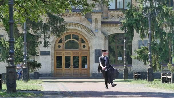 Happy Graduand Jumps Throws Hat up Walking University Courtyard Young Man in Student Mantle Old Brick Building Surrounded With Park Sunny Green Trees
