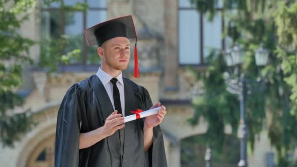 Graduand in Mantle Thinking Holding His Diploma Standing in Alley Outside the Univesrsity Inspired Student Nods His Head Sunny Summer Day Green Trees