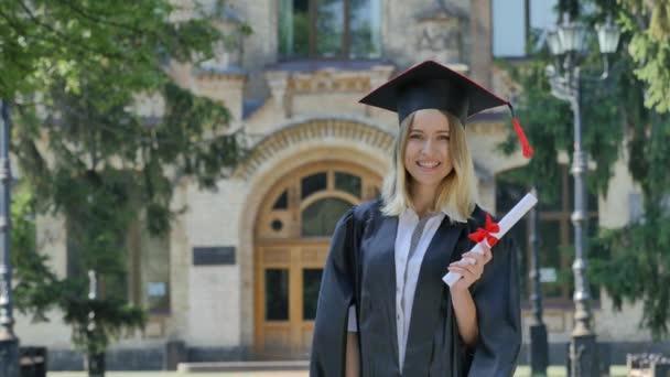 Absolventa ženy v Mantle zobrazí její palec držení diplomu usmívající se stát v uličce před Neivesrzností šťastný maturita a koktejly v roce slunného léta