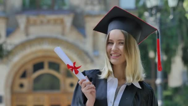 Maturita, která dokládá její diplom usmívající se stát v uličce před Neivesrzností šťastný maturita a třese s diplomem slunného letního dne zelené stromy