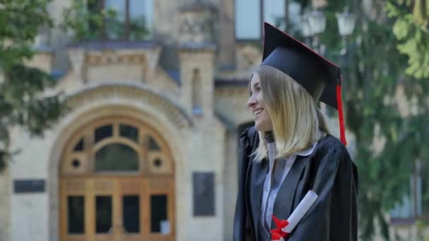 Happy Woman in Mantle Shows Her Diploma Man Comes Smiling Kisses the Woman Standing in Alley Outside the University Happy Graduands in Sunny Summer Day