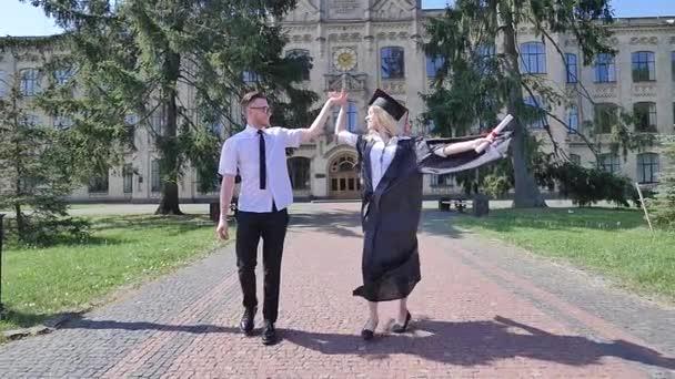 Šťastné absolventy držení žena se kroutila usmívající se ženou v Mantleových mužích v košili a kravatě chůze v uličce mimo univerzitní pár za slunečného dne