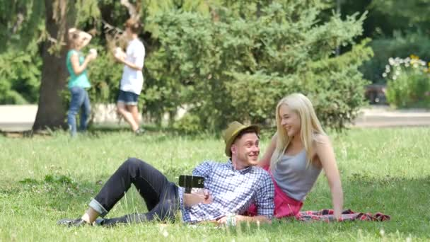 Couple Have Picnic Taking Photos on a Lawn Posing Sitting on a Green Grass in Park Teenagers Lying on a Lawn at the Nature Friends Couples Summer Day