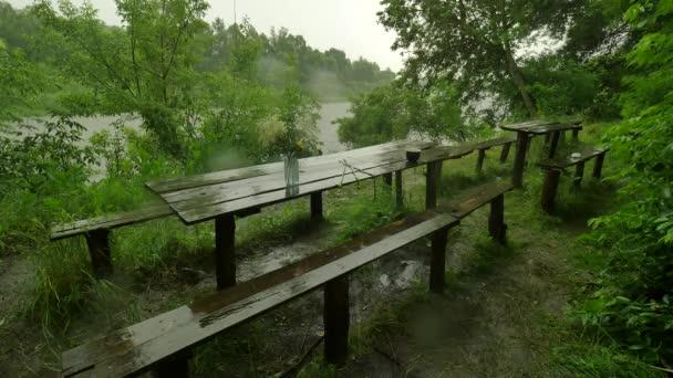 Staré dřevěné stoly a lavice v lití déšť turistické základny svěží zelené stromy lesa dešti je mytí Off všechny stopy zataženo deštivé letní den na řece