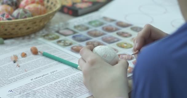 Girl Draws On Easter Egg With Pencil Painted Easter Eggs In Wicker Basket Technology Of Painting On Easter Egg Painting On Easter Egg By The Sketch
