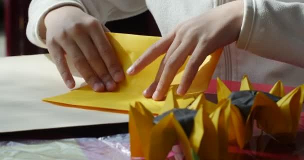 Dítě dělá slunečnice z barevného papíru dva papírové slunečnice na tabulka Origami soutěž takže kusudama sestavit Close Origami Origami Modulární jednotka