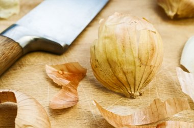 Onion peelings, knife and wood cutting board in the background