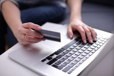 businesswoman using his credit card for an online transaction,Businessman using his credit card for an online transaction