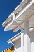 Nové dešťových svodů na domácí proti modré obloze bílé