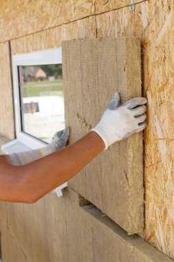 Builder worker installing  insulation material on a wall