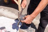 Dělník vyrábí střešní břidlice pomocí břidlicové kladivo
