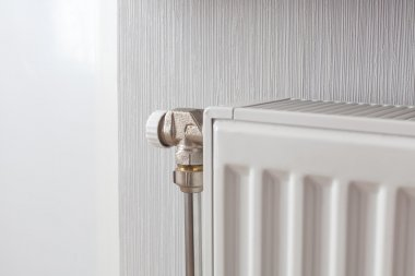 Heating white radiator with adjuster of warming in living room.