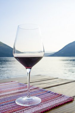 Close up view of the glass of red wine against blue sea and mountains during golden hour at sunset. Dinner on terrace in cafe.