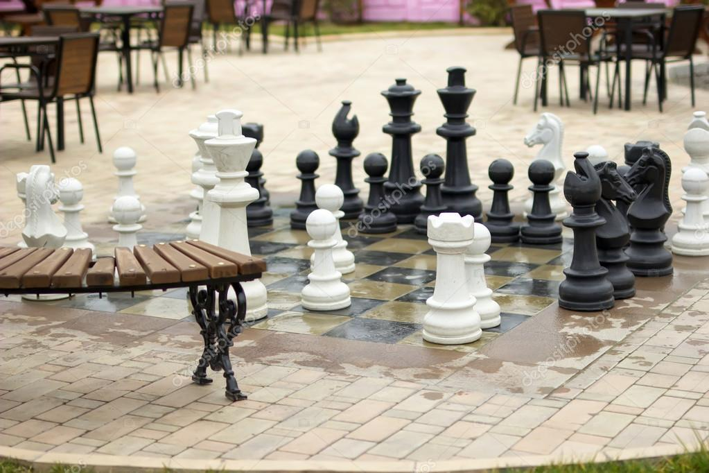Park with chess figures autumn season. Big chessboard outdoor in tropical resort.