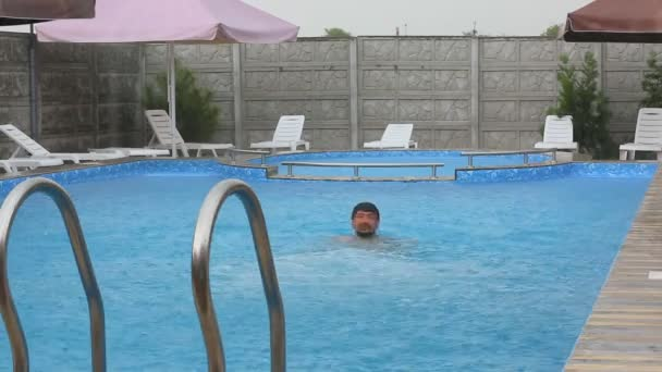 Man floating on water in swimming pool.Young man relaxing in the swimming pool onrainy day