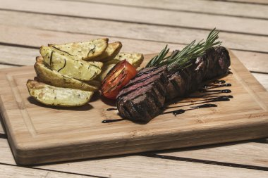 Delicious beef steak on wooden table, close-up. Grilled veal steaks with vegetables on cutting board.
