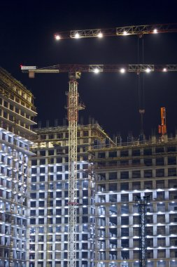 Lots of tower cranes build large residential buildings at night. buildings under construction with cranes and illumination at dark night. night shot of construction equipment at building site.