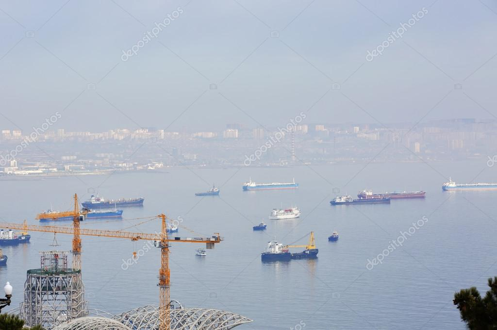 Bird's-eye view seascape with cargo ship in the morning misty weather. Different types of ships. Top view. A lot of cargo ships in Caspian sea, Baku, Azerbaijan.