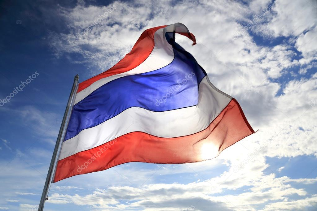 Thailand flag waving in the wind with beautiful blue sky and sunlight