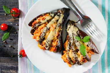 Baked eggplant with cheese, tomatoes and chicken on a dark woode