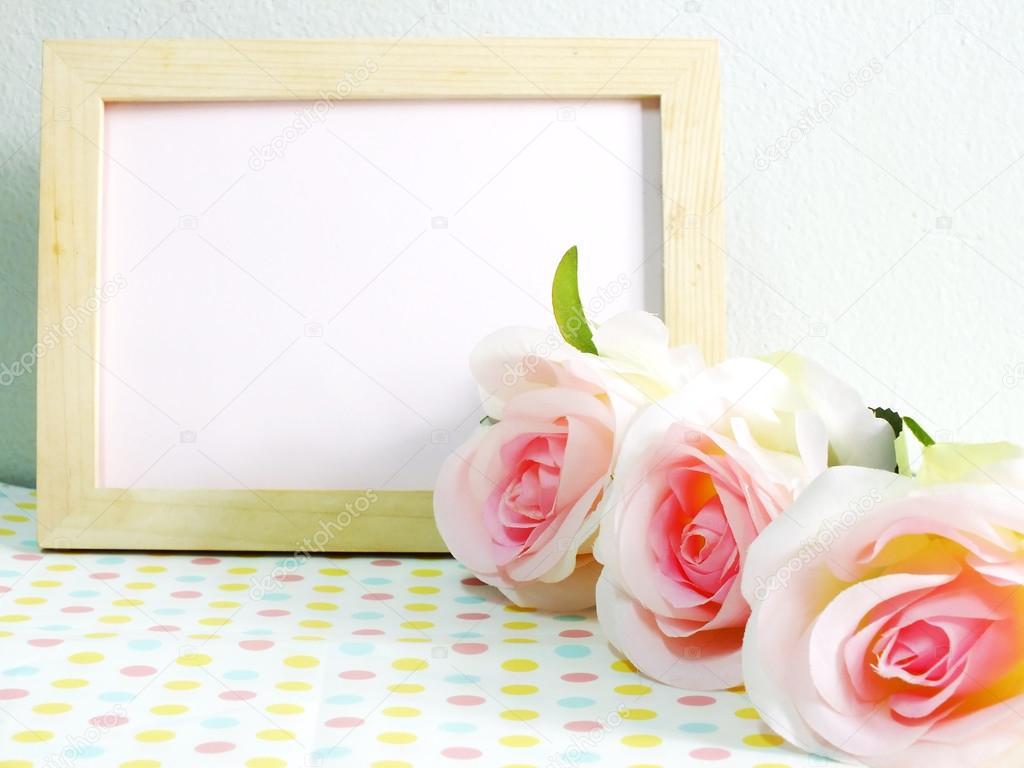 Leere Holz-Fotorahmen mit rosa Rosen und Geschenk-Box auf süße Blume ...