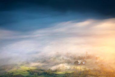 Beautiful sunrise view from the top. Green misty meadow covered with morning fog and clouds. stock vector