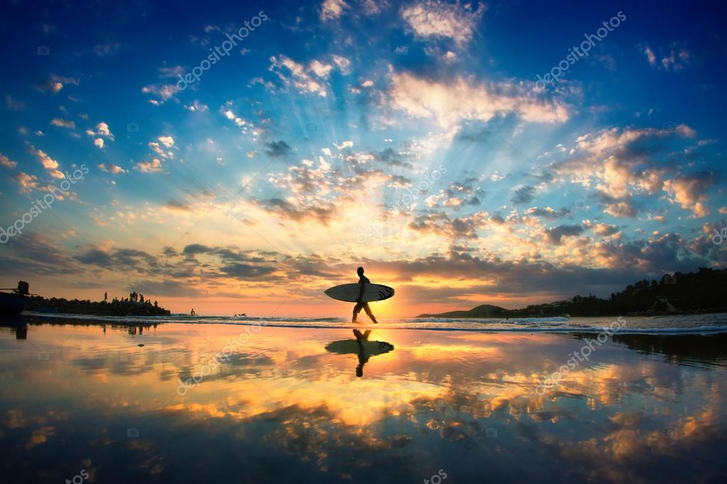 Sun surfer walking across the sea shore