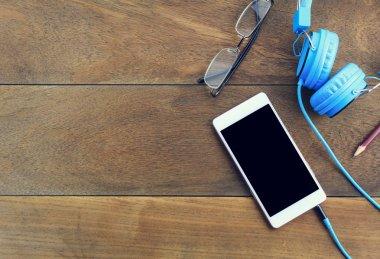 smartphone or mobile phone,eyeglasses,pen,note,blue headphones on wood table.