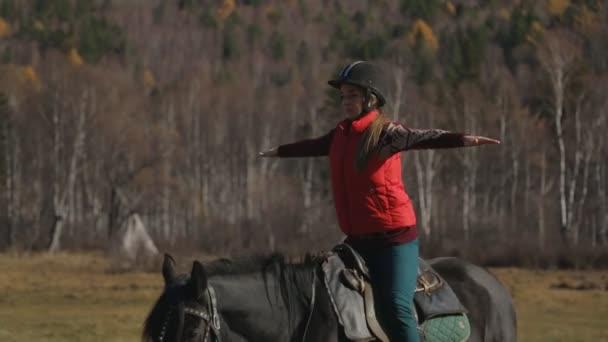 die Frau lernt, ein Pferd richtig zu reiten, um das Gleichgewicht zu halten, indem sie ihre Hände parallel zum Boden hält.