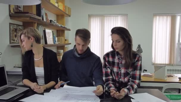Three young people in the office discussing results presented in graphs and charts