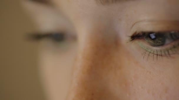 To je obrázek mrkající oči ženy pracující. Názor je soustředěna na zařízení, které odráží