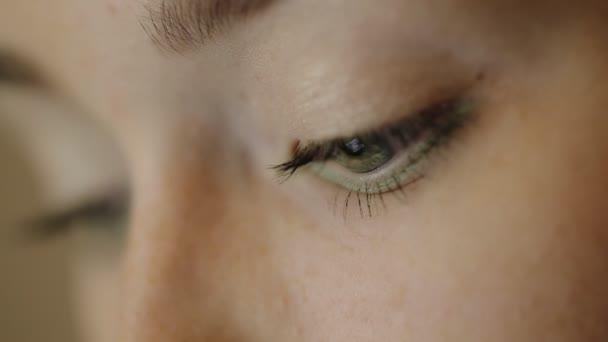 Existují mrkající oči žena pracující s digitální zařízení, které se odráží v jejím pohledu