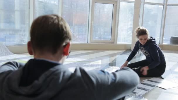 Dvě osoby sedí na dlažbu a práce s výkresy