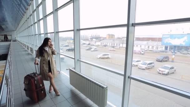 Geschäftsfrau telefoniert am Flughafen in Abflughalle