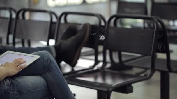 Frau sitzt auf schwarzem Stuhl im Flughafen und spielt mit Touchpad