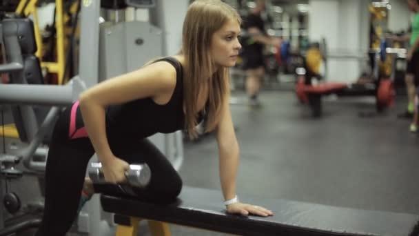 Žena v tělocvičně zvedání činka na lavičce