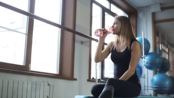 Mladá žena má zbytek pitné vody v tělocvičně