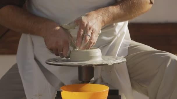Meister töpfert auf Töpferscheibe in Werkstatt