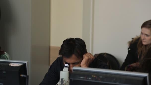 Kostým Indián vypadá přes mikroskop v učebně biologie.