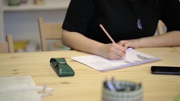 Na dřevěný stůl je mobil, brýlové pouzdro, list papíru na který žena čerpá