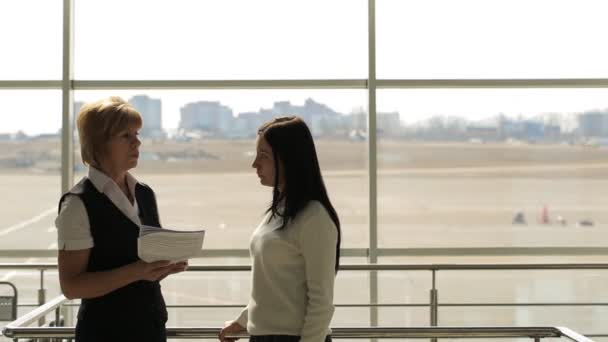 zwei Frauen unterhalten sich in der Wartehalle des Flughafens