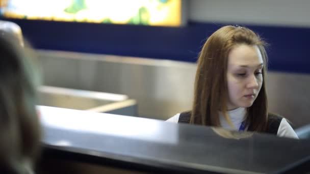 Sedět v Letiště mladá žena pracuje s dokumenty klienta
