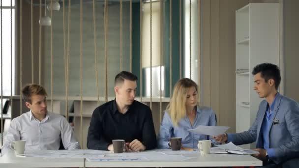 Muž v obleku sako dát přes řetěz, Žena dokumentů a dalších lidí, kteří sedí u stejného stolu