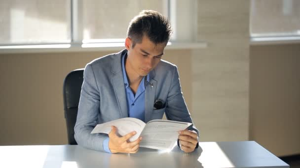 A young man in a suit jacket running notary flipping through documents in office with a table on which shines sun.