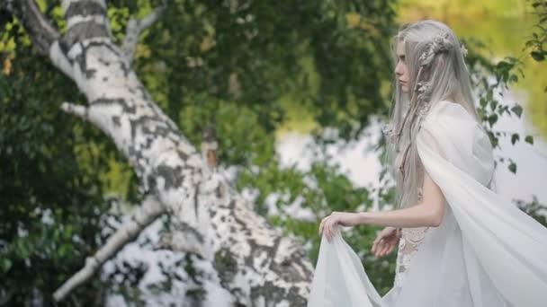 Krásný model s šedými vlasy zůstává na břehu jezera.